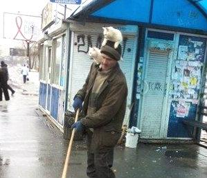 В Киеве дворник носит котов на голове.